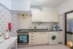 Kitchen with appliances and utility room/storage.