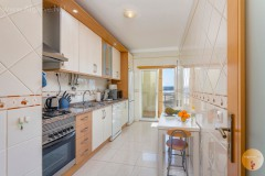 Large kitchen with lots of equipment and access to the balcony.