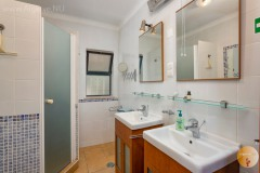 Family bathroom with shower, toilet, and washbasins.